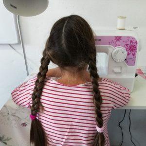 Mädchen mit Zöpfchen an der Nähmaschine